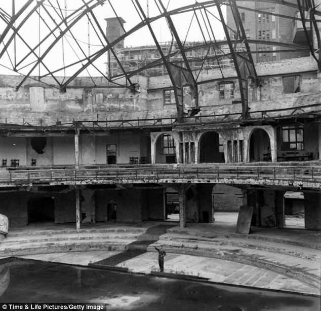 It's pver: A U.S. soldier, PFC Douglas Page, offers a mocking Nazi salute inside the bombed-out ruins of the Berliner Sportspalast where the Third Reich often held political rallies