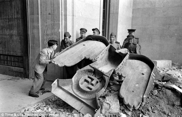 Heavy work: Russian soldiers and a civilian struggle to move a large bronze Nazi Party eagle that once loomed over a doorway of the Reich Chancellery, Berlin, 1945