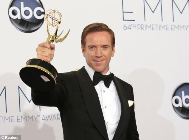 Damian Lewis holds up the award for outstanding lead actor in a drama series for his role in Homeland at the Primetime Emmy Awards in Los Angeles in September