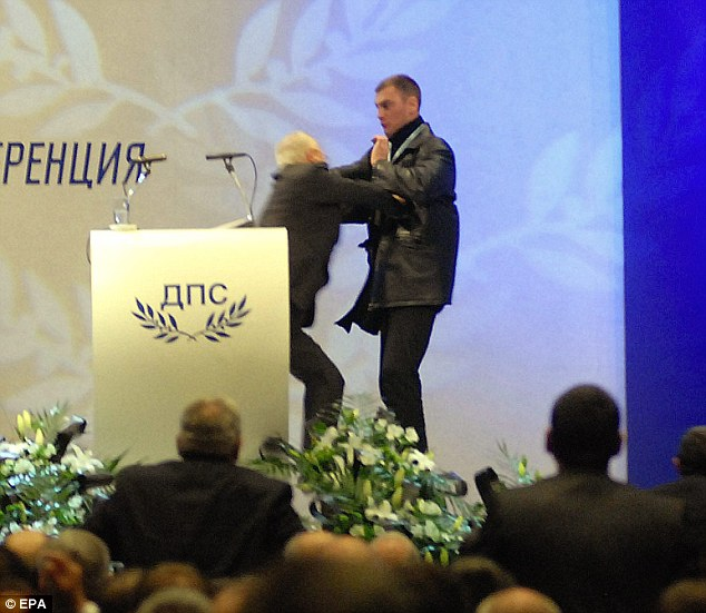 Mr Dogan is left to fend for himself on the stage after the gunman approached at the conference centre in Sofia