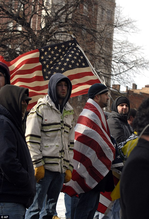 Symbols: Keeping warm while maintaining their patriotism, a demonstrator wrapped himself in an American flag among others being waved