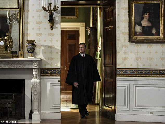 Reading it carefully: Chief Justice John Roberts famously floundered when he read the oath of office to Mr Obama in 2008, but he was careful to make no mistakes this time around