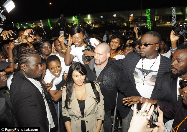 Mobbed: Pregnant Kim was mobbed by fans as she arrived on the Ivory Coast on Friday