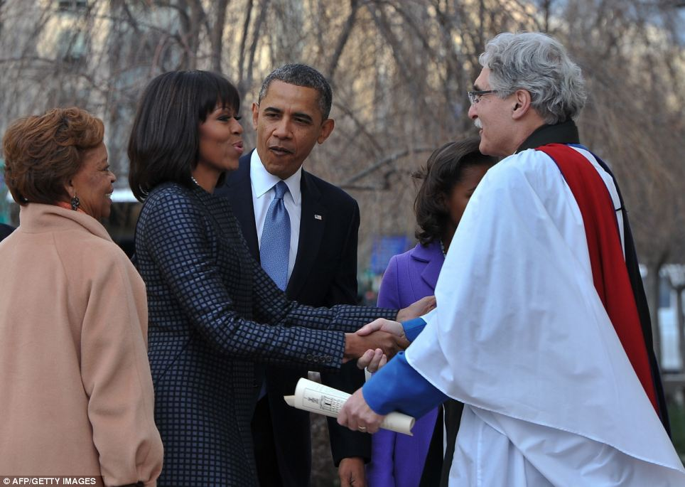 Welcome: The Obamas are greeted by Rev. Luis Leon as they arrive at St. John's Church on Monday