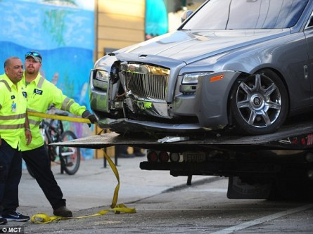 Evidence: Rick Ross' bullet-riddled Rolls Royce is taken away for study by police forensic officers after the drive-by shooting in Floria early on Monday morning