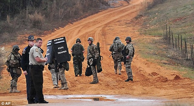 Out in force: Dozens of local police officers, Alabama State Police troopers and federal agents from the ATF and FBI swarmed the area where the boy was being held captive