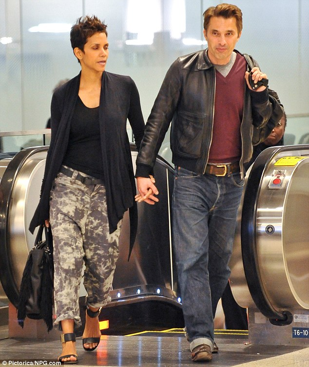 Still stylish: Halle wore baggy camo pants paired with layers of black for a comfortable flight