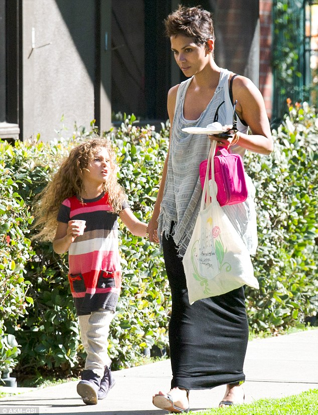 Snack time: The little girl held a small cup while Halle carried a plate along with a handful of bags
