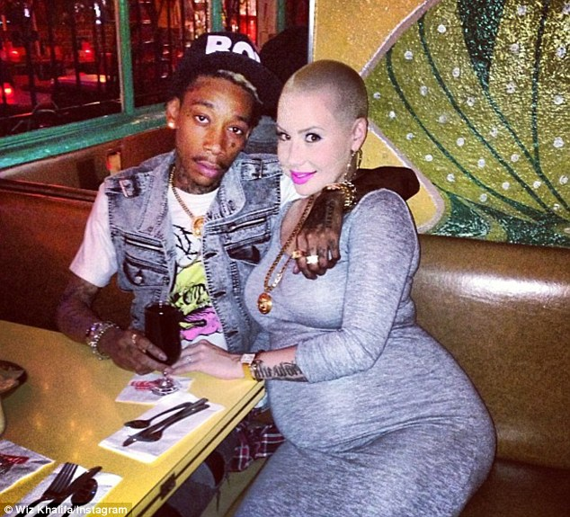 Wrapping his arms round his baby mama: Rapper Wiz Khalifa posted a photo of he and his pregnant fiancee Amber Rose to Twitter Monday