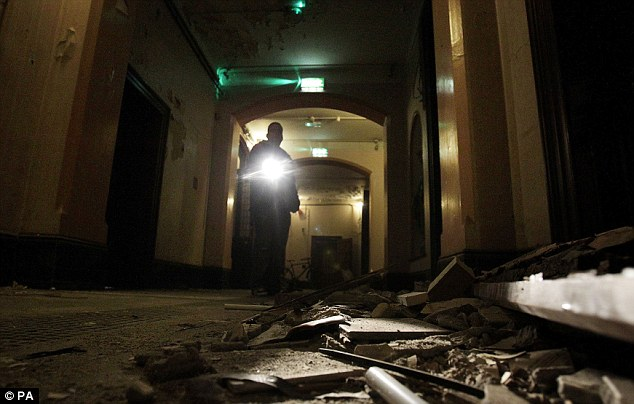 Un trabajador del Consejo, brilla una antorcha sobre los desechos en el suelo del pasillo de las Hermanas ahora abandonado de Nuestra Señora de la Caridad Magdalena lavandería en Dublín