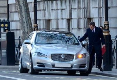 Taking a ride: Welsh Secretary David Jones gets into a chauffeur-driven Jaguar XJ that ferried him 100 yards to Downing Street