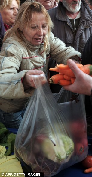 A woman fills a plastic bag with tomatoes, salad and carrots from a protesting farmer