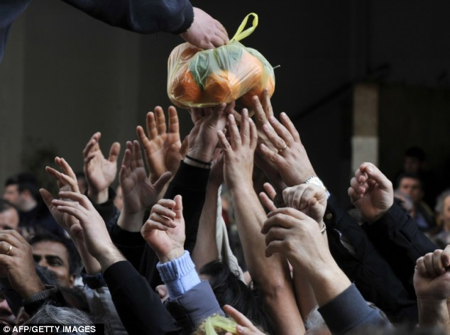 Large haul: Dozens of hands reach out for a bag of oranges as farmers gave away more than 50 tons of fruit and vegetables