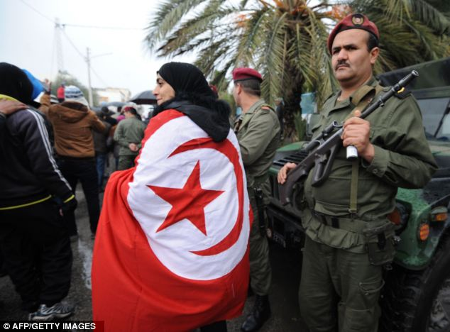 Respect: A woman wrapped in a national flag walks past a Tunisian soldier standing guard