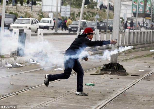 Battle: A protester throws a tear gas canister, which was earlier thrown by riot police. Youths battled police in violent clashes and stole from mourners at the funeral