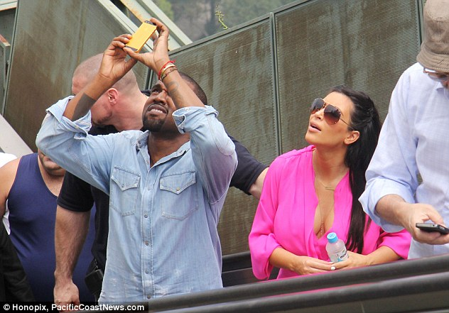 Got it covered: Kanye snaps another shot from a different angle