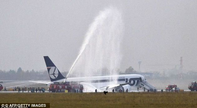 Rescue: Fire engines spray fire retardant foam on the LOT Polish airlines plane after it comes to a standstill. Astonishingly none of the 230 people on board were injured
