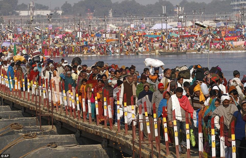 До массового обслуживания: Тысячи индийских преданных индуистской идти через понтонный мост на Sangam перед купанием