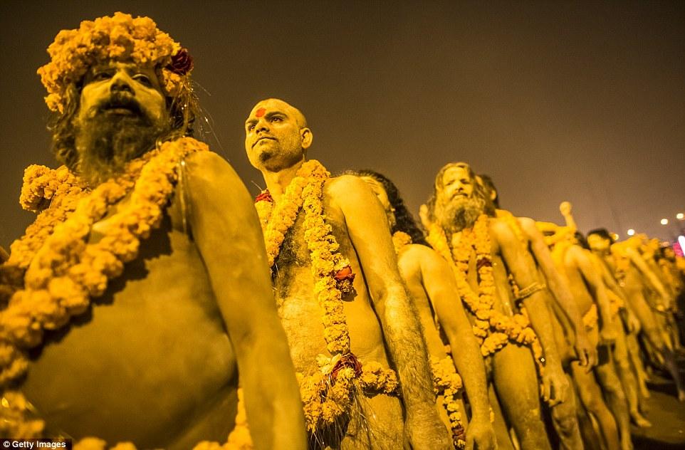 Стоя в линии: Naked индуистские святые процесса на купание день Mauni Amavasya