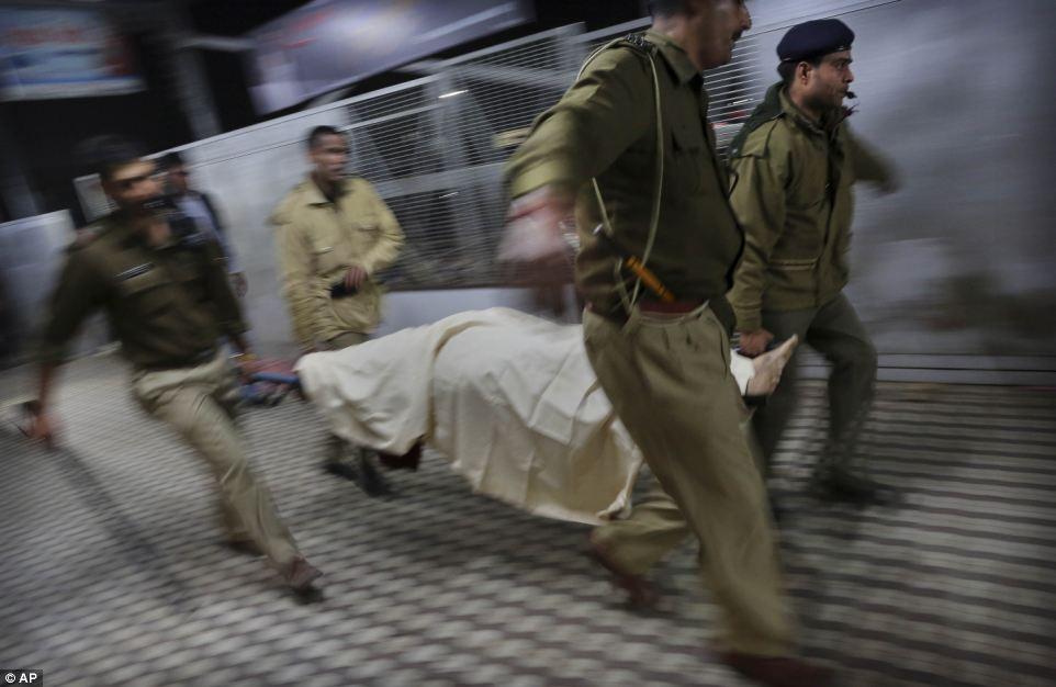 Грим: Индийская полиция несут тело паломника, который был убит в Аллахабаде