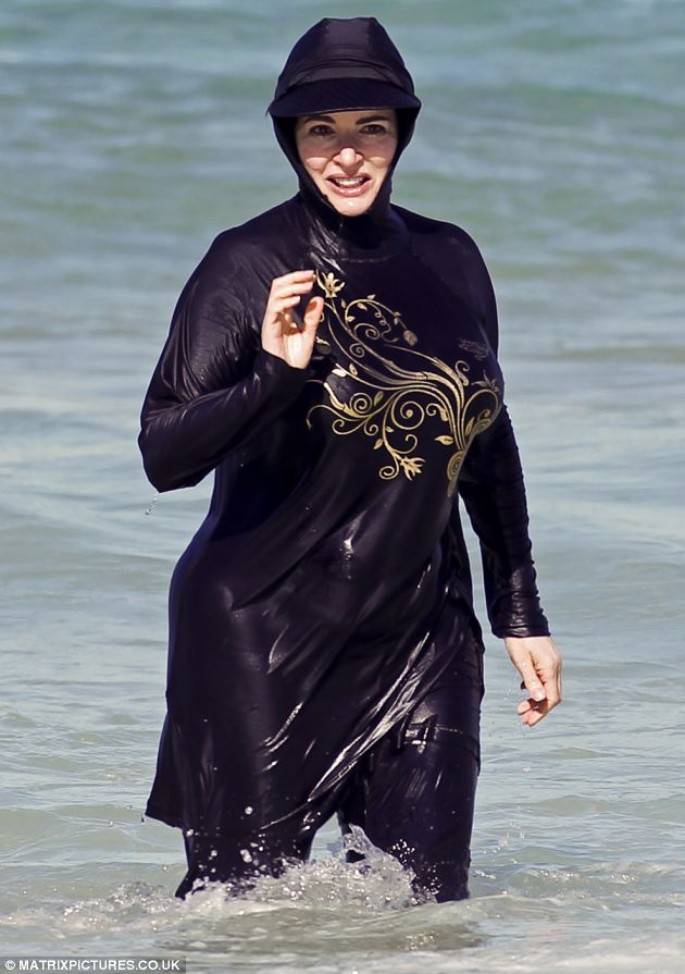 TV chef Nigella Lawson playing in the surf on Bondi Beach in Sydney, Australia in a full body burkini style swimming outfit