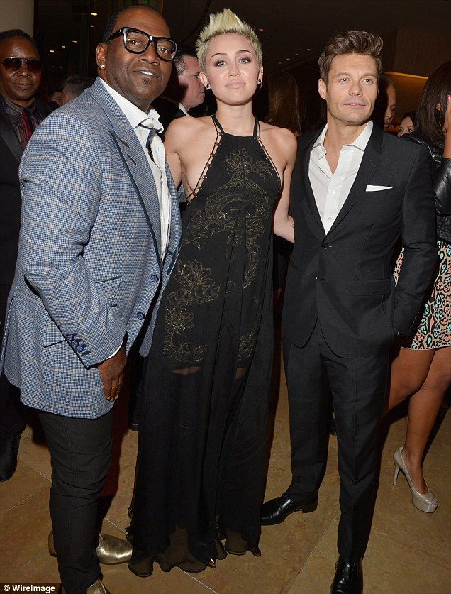 Miley's men: Cyrus posed with L.A. Reid and Ryan Seacrest inside the Beverly Hilton