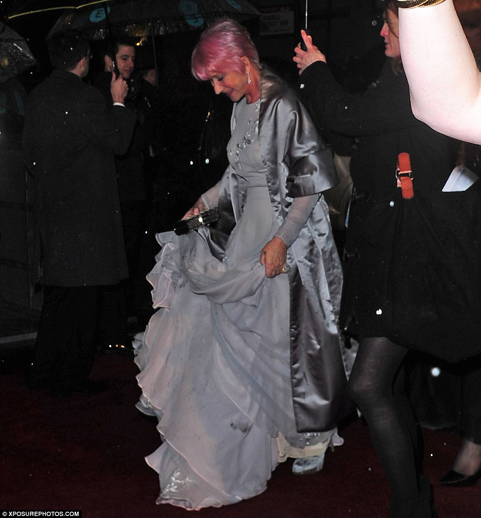 Mind the dress: Helen Mirren was seen covering up in a silver satin coat as she had her own umbrella holder throughout the red carpet proceedings