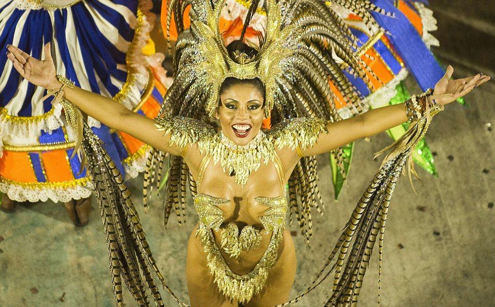 Перья и блестки: гуляка из школы самбы Portela выполняет в первую ночь карнавала парад