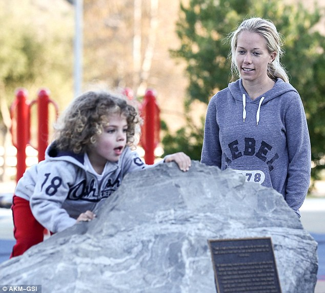 Big boy adventure! The curly-haired three-year-old matched his famous mother in a grey hoodie and red athletic trousers as he gleefully climbed a boulder