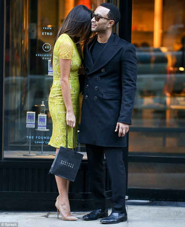 Stunning couple: Teigen looked gorgeous in a bright green lace dress as she leaned on her dapper fiance