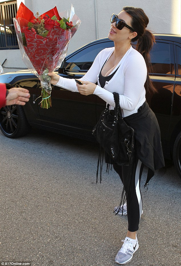 Smelling of roses: Kim Kardashian was greeted with a bouquet of flowers as she left the gym in Los Angeles on Valentine's Day