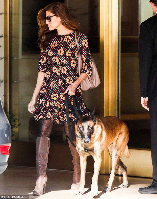 Pretty as a flower: Eva looked lovely in a bright and bold floral print dress and knee-high brown platform boots