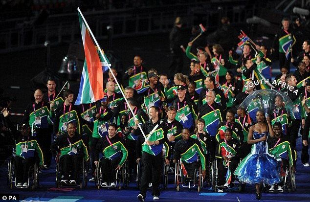 Flying the flag: Pistorius leads out his fellow South Africans at the Paralympics