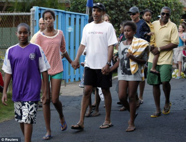 The president walks with daughters Sasha and Malia while on holiday in Waimanalo, Hawaii at Christmas