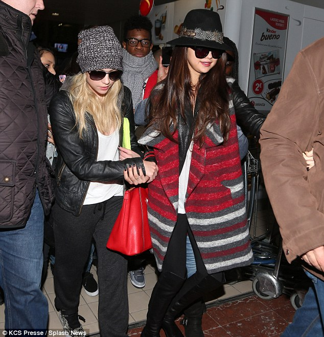 Hold my hand: Selena Gomez and Ashley Benson held on to each other as they touched down in Paris attend French premiere for Spring Breakers