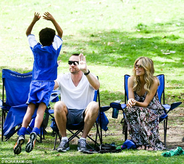 Team players: Heidi smiled in approval as her beau gave her son Henry a double high five