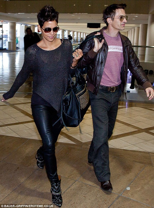 Those boots were made for walking: Halle Berry rocked a pair of Isabel Marant Milwauke studded suede and leather ankle boots as she strutted through Los Angeles airport with fiance Oliver Martinez on Sunday