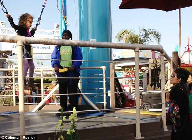 Up, up, and away: Halle Berry looks on with pride as her daughter Nahla bravely jumps on a bungee ride at Santa Monica Pier in Los Angeles on Monday