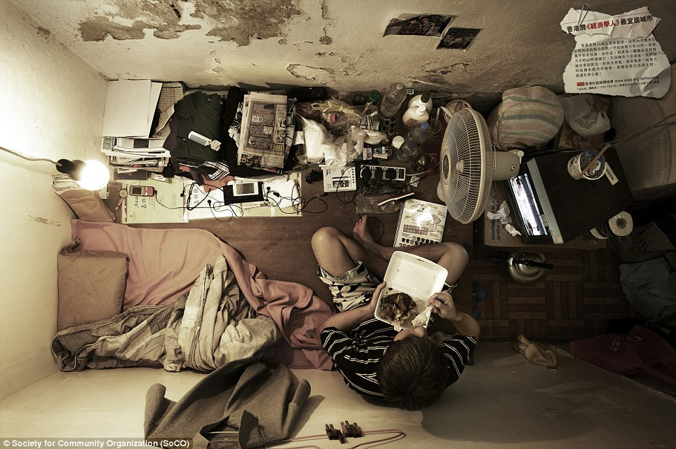 No standard of living: A man tucks into a takeaway as the walls of his room flake off around him. He has no proper bed to speak of