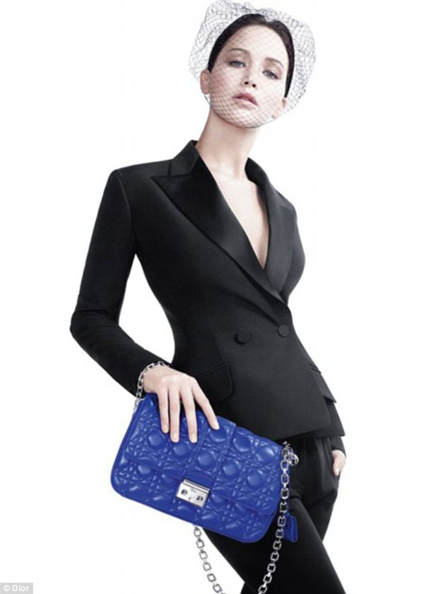 She's no bag lady: Jennifer is seen in a suit holding up a brightly coloured bag from the new Miss Dior collection