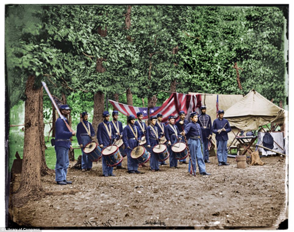 In living color: This colorized image of the band more clearly shows off the different blues of their uniforms and the dirty conditions they were forced to line in