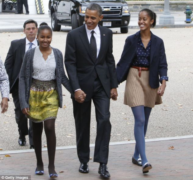 Protective: Obama is pictured with his daughters Sasha, left, and Malia, right, in Washington D.C in 2012