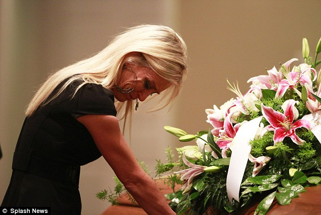 Mourning: Jill Stancel places her hands on the coffin of Mindy McCready as her music played in the background and her image was shown on a large screen behind the altar