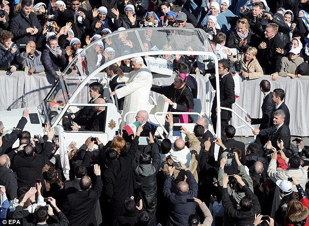 The pontiff makes his way through the crowds in his 'Popemobile'. He will officially resign at 8pm tomorrow