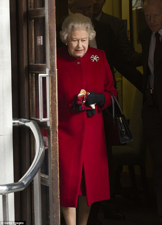 With a handbag over one arm, and clutching a neck scarf and one glove as she prepared to shake the hands of waiting hospital staff, the Queen emerged in good spirits