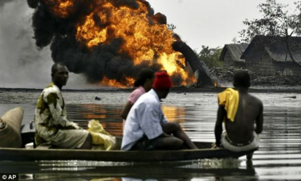 People evacuate their homes by boat, as they past a burning oil pipeline in Asagba Okwan Asaramav southwest of Port Harcourt, Nigeria