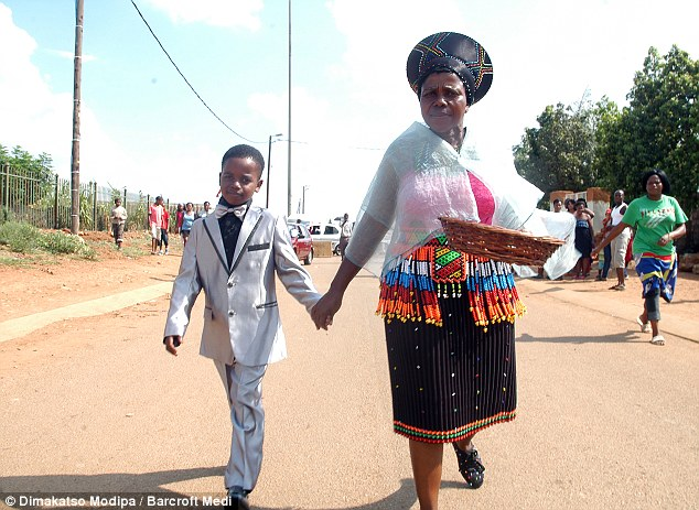Given away: Sanele walks to his wedding with his mother as people look on. The ceremony shocked some people in the community