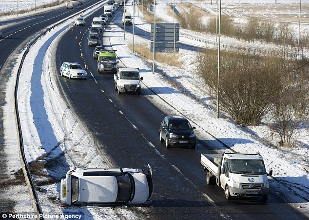 Accident: A car lies on its side on the snowy A90 at Inchture, between Perth & Dundee, causing big tailbacks