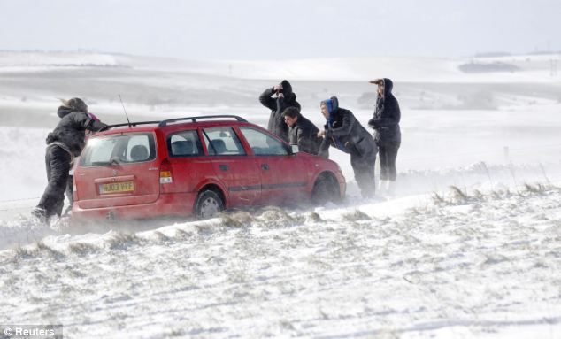Hard at work: People try to move a car stuck in snow on the South Downs near Brighton