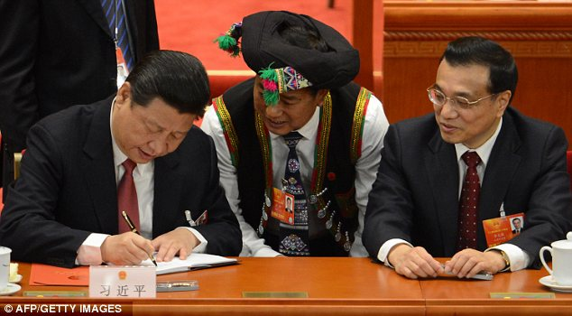 Power: China's new president Xi Jinping, left, and vice-premire Li Keqiang, right, sign autographs